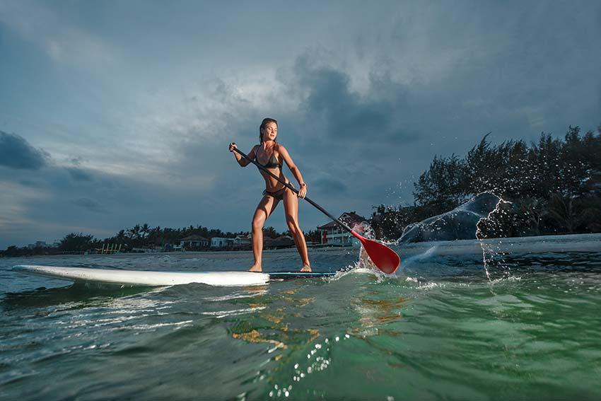 Kako supati? Ženska na SUPu z veslom po vodi