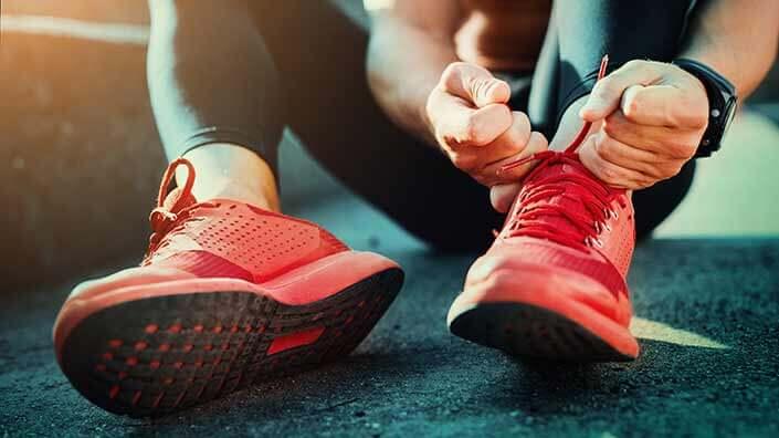 MOški tekač si zavezuje tekaške copate