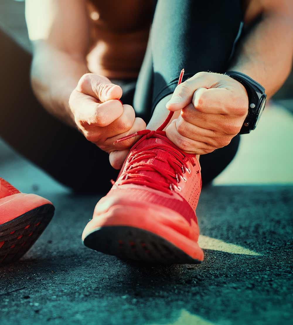 Moški tekač si zavezuje tekaški copat na testu tekaških copat